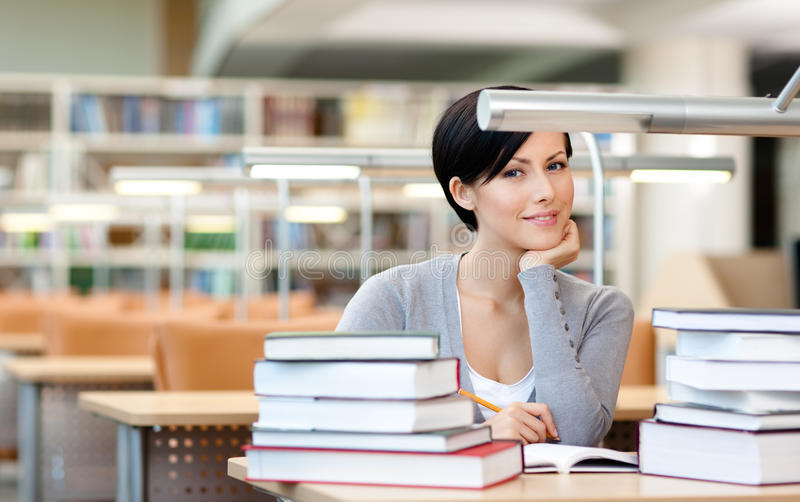 Smiling female student studies at the reading hall royalty free stock photos