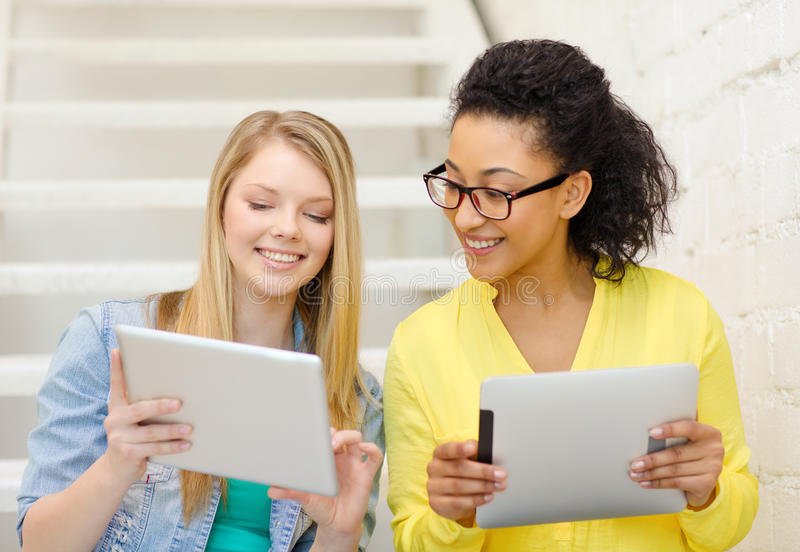 Smiling female students with tablet pc computer. Education and technology concept - smiling female students with tablet pc computer sitting on staircase royalty free stock image