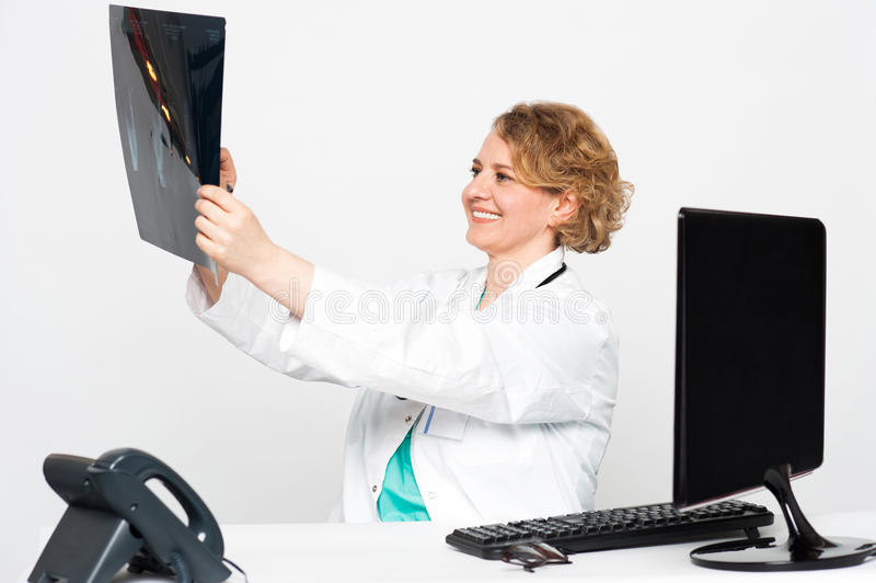 Smiling female surgeon looking at patients x-ray