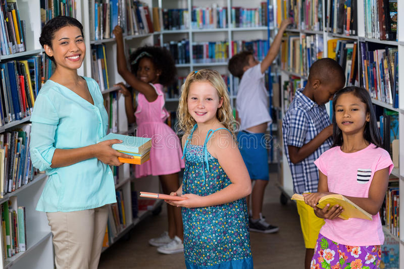 Smiling female teacher giving books to girl royalty free stock photo