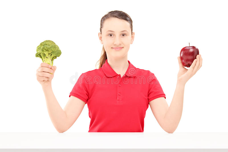 Smiling female teenager sitting and holding apple and broccoli stock photos