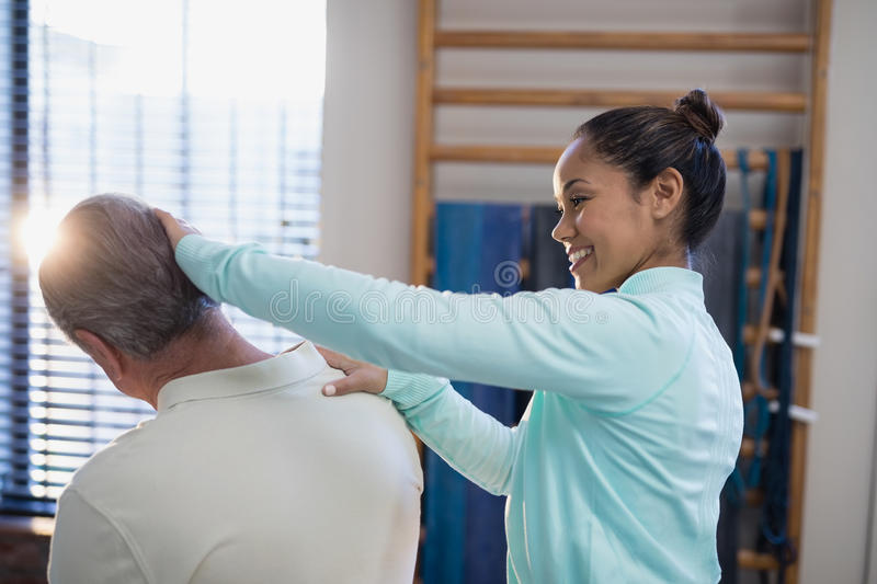 Smiling female therapist examining neck of senior male patient stock images