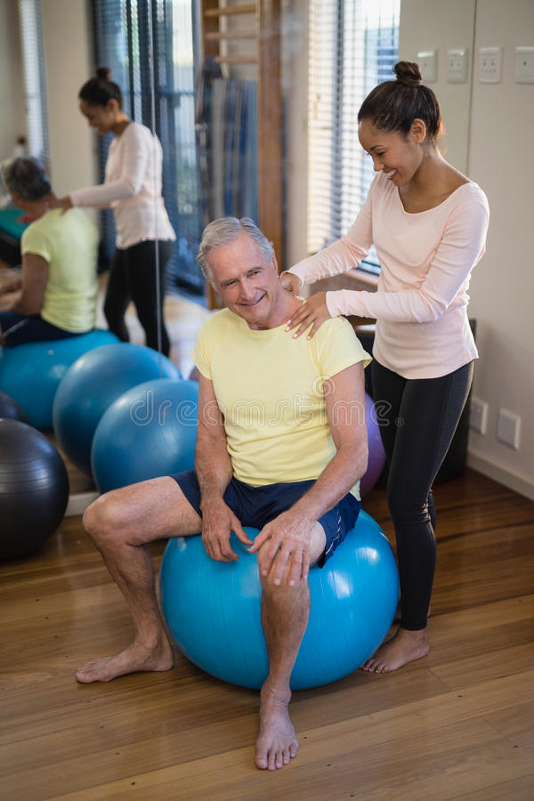 Smiling female therapist giving neck massage to senior patient sitting on exercise ball against mirr. Or at hospital ward royalty free stock photos
