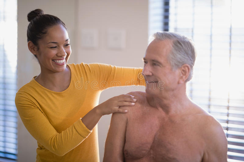 Smiling female therapist giving neck massage to shirtless senior male patient at hospital ward stock photography