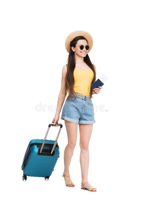 Smiling female traveler with passport, air ticket and baggage,. Isolated on white stock images