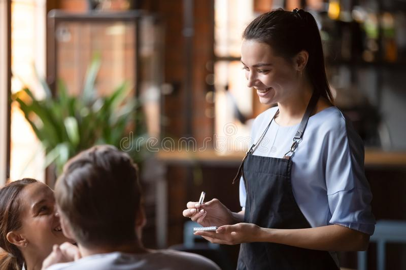 Smiling female waitress take order talk to clients couple royalty free stock photography