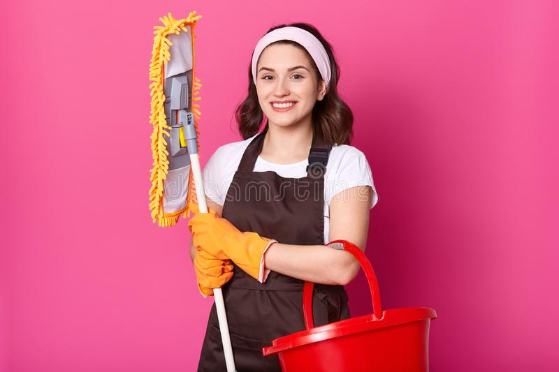 Smiling female wears brown apron and yellow rubber gloves, holds mop and red bucket. Young woman cleans house. Beautiful girl does royalty free stock photography
