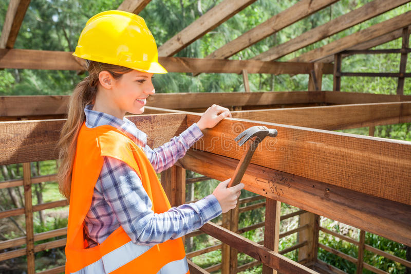 Smiling Female Worker Hammering Nail On Timber royalty free stock photography
