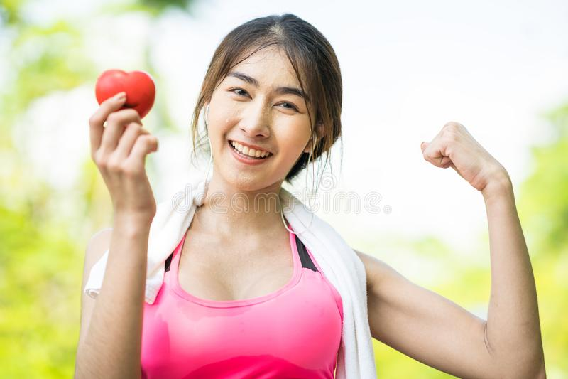 Smiling female after workout, She holding red heart ball. For healthy meaning royalty free stock photo