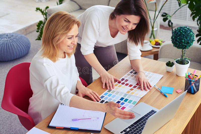 Download Smiling Females Working With Catalog Of Color Palette And Laptop Stock Photo - Image of communication, ideas: 92490800