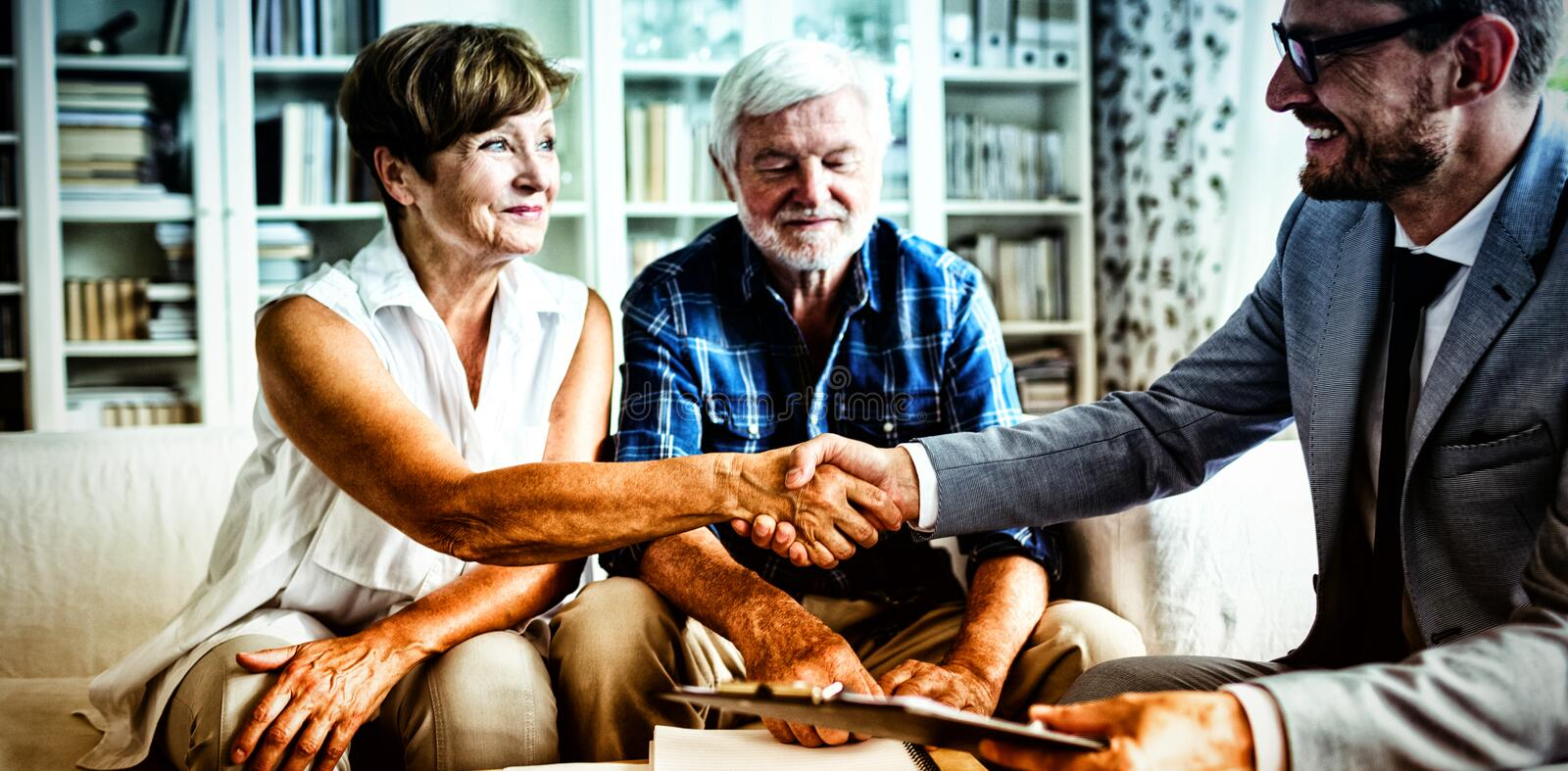 Smiling financial advisor shaking hands with senior woman. Smiling financial advisor shaking hands with senior women in living room royalty free stock photo