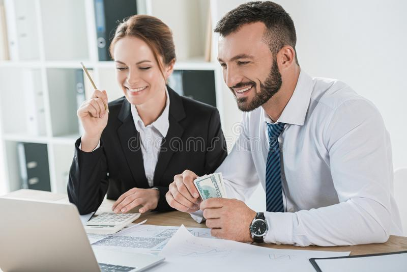 Smiling financiers counting money and looking at laptop. In office royalty free stock images