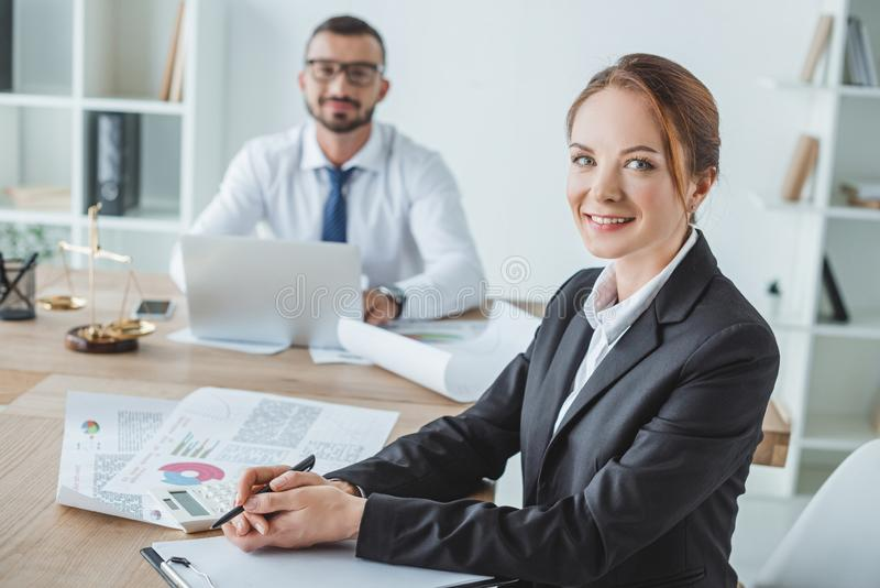 Smiling financiers looking at camera. In office royalty free stock image