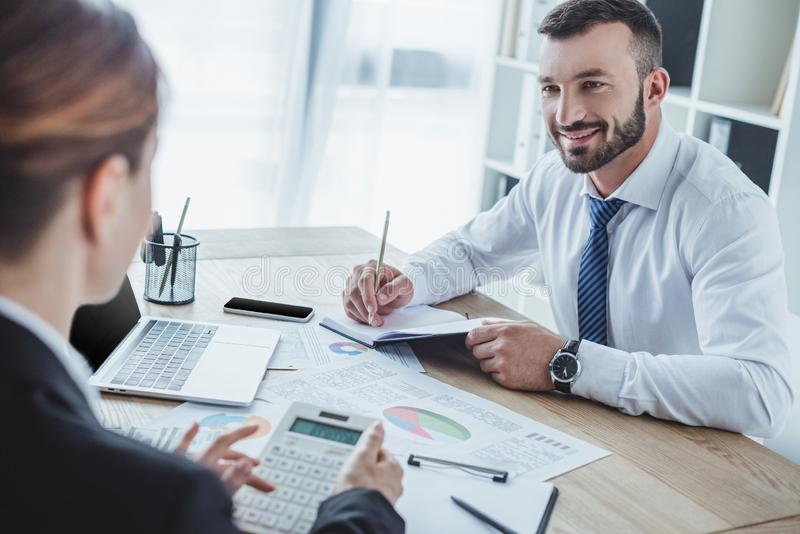 Smiling financiers looking at each other during work. In office stock photo