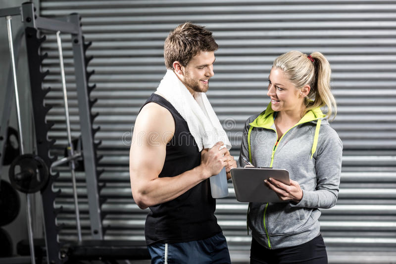 Smiling fit couple taking notes. At crossfit gym stock image