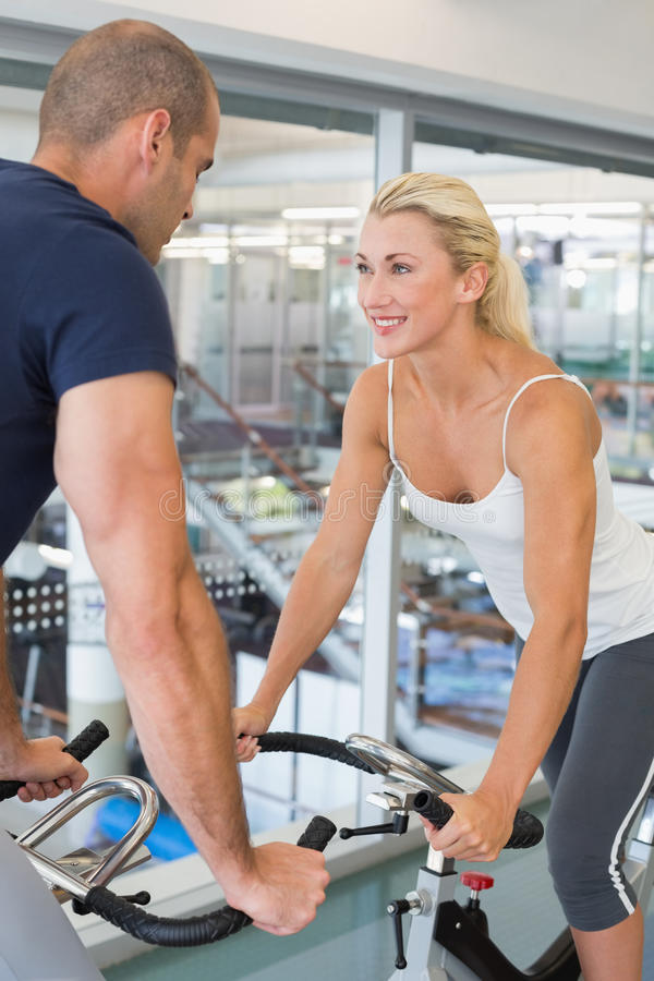 Smiling fit couple working on exercise bikes at gym stock image