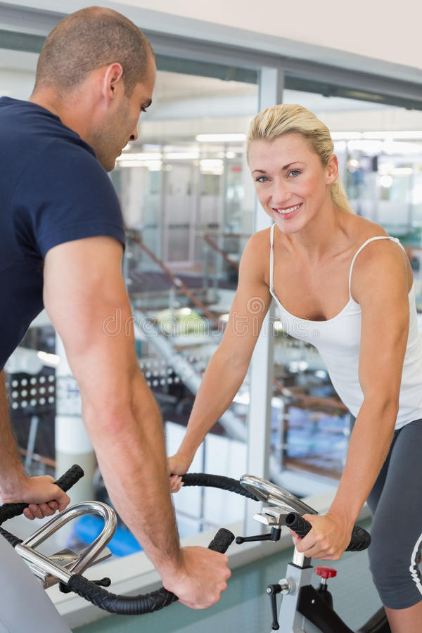 Smiling fit couple working on exercise bikes at gym royalty free stock photography