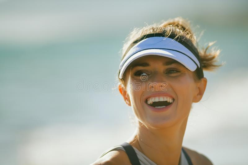 Smiling fit sports woman on seacoast in evening. Portrait of smiling fit sports woman in fitness clothes on the seacoast in the evening. beautiful summer day. 30 royalty free stock image