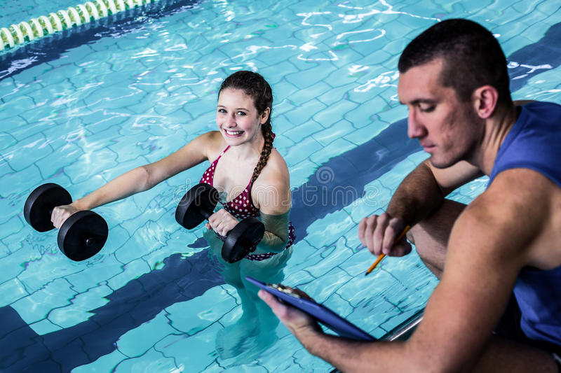 Smiling fit woman doing aqua aerobics. Smiling fit women doing aqua aerobics with trainer stock photo