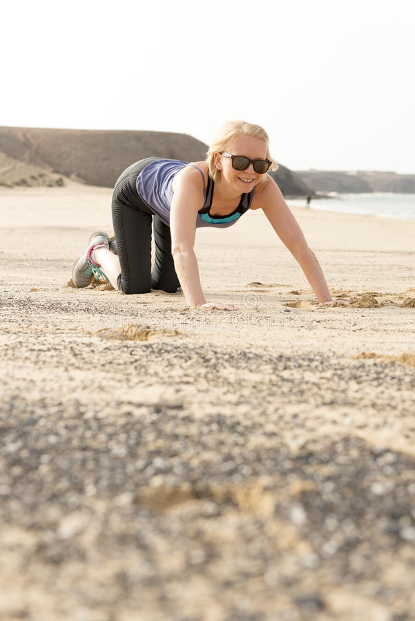 Smiling Fit Woman Doing Push-Ups by the Beach royalty free stock image