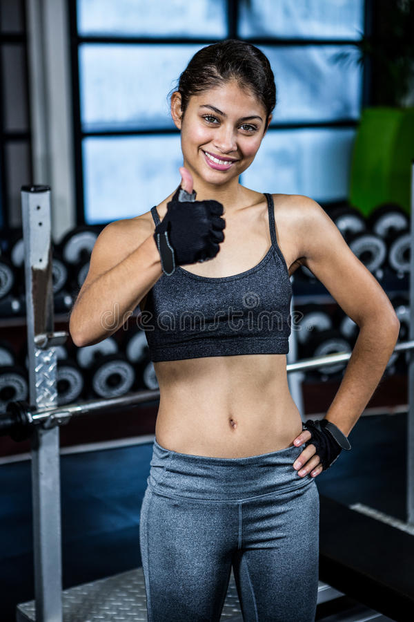 Smiling fit woman with thumbs up royalty free stock photos