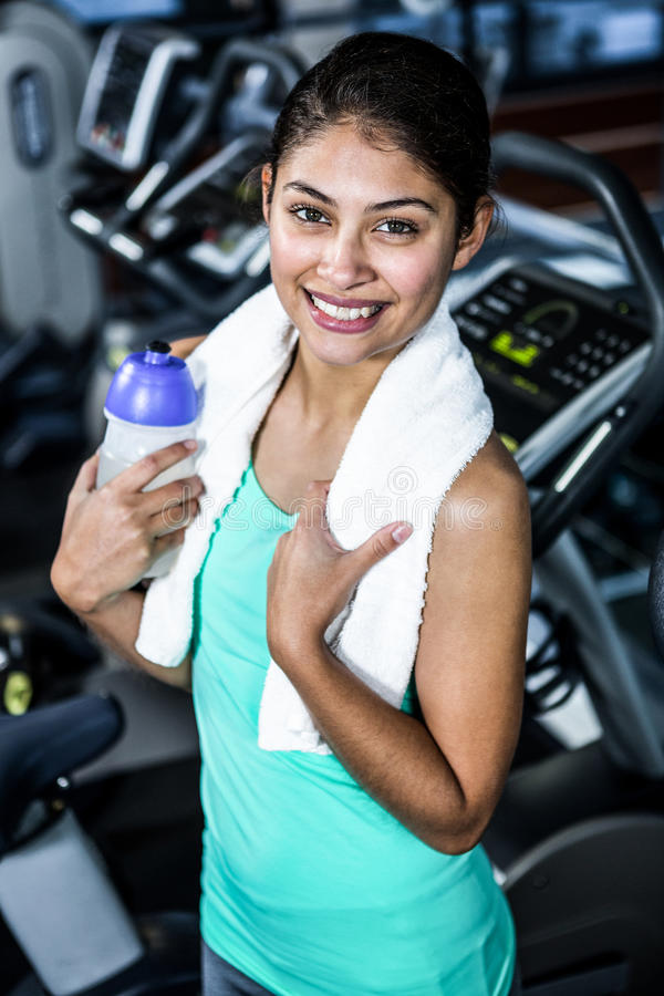 Smiling fit woman with towel and water stock image