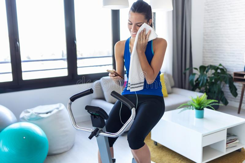 Smiling fitness girl using mobile phone after training on exercise bike at home royalty free stock photography