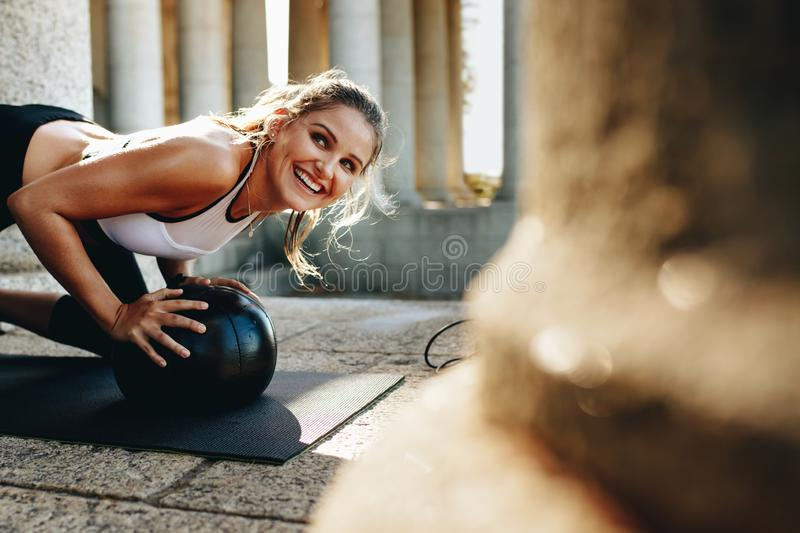Smiling fitness woman doing workout using a medicine ball royalty free stock photo