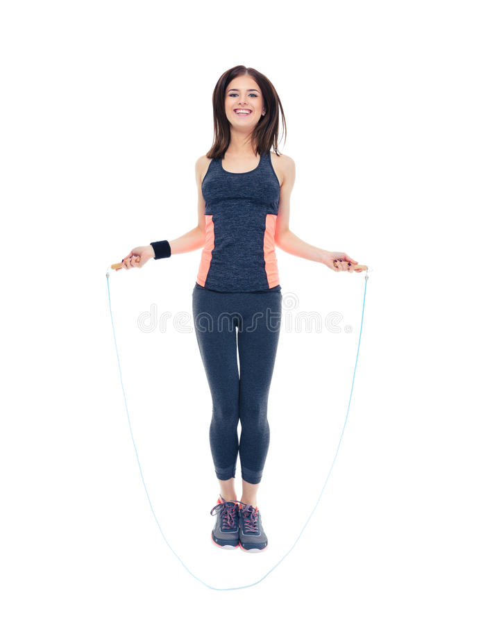 Smiling fitness woman jumping with skipping rope. Full length portrait of a smiling fitness woman jumping with skipping rope isolated on a white background stock photography