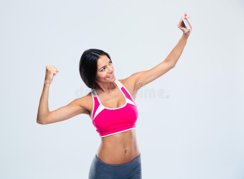 Smiling fitness woman making selfie photo. On smartphone over gray background royalty free stock image