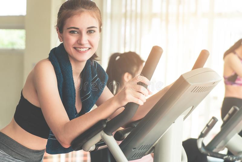 Smiling Fitness woman is running on treadmill with friends stock photography