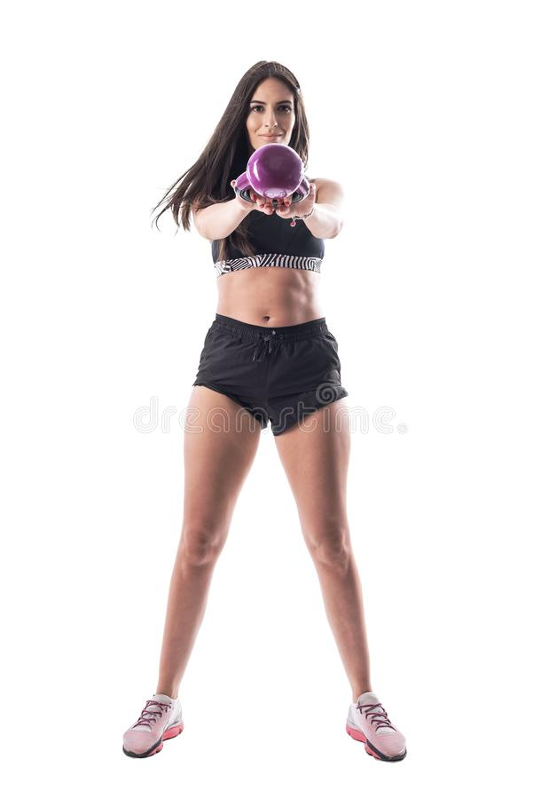 Smiling fitness woman in sport clothes doing kettlebell exercise effortless. stock images