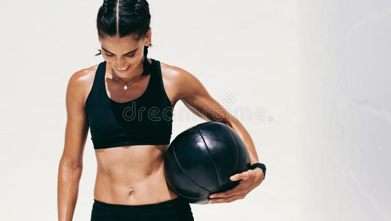 Smiling fitness woman standing with a medicine royalty free stock images
