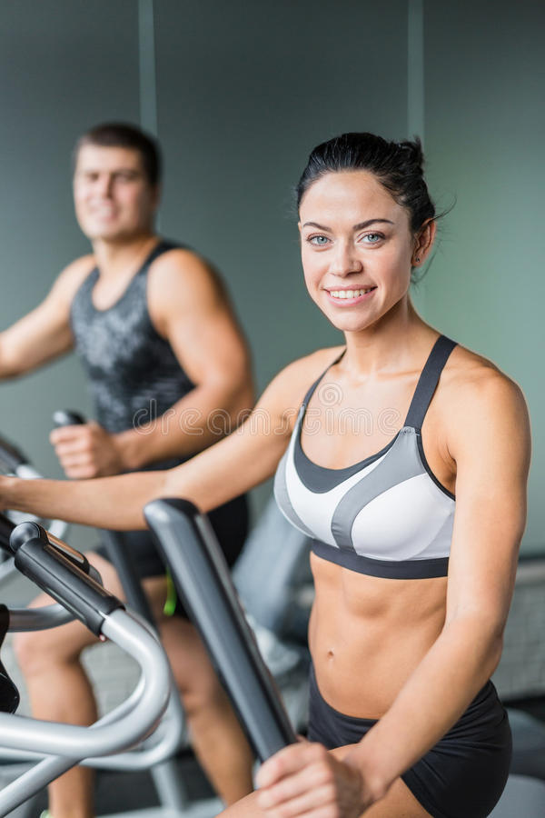 Smiling Fitness Woman Using Elliptical Machine in Gym stock photo