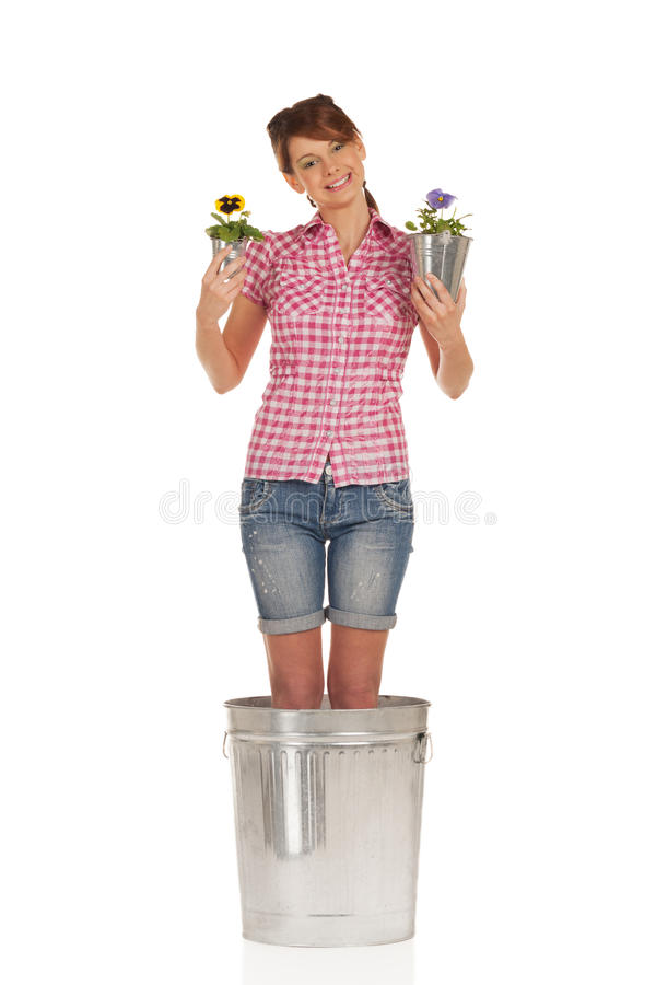 Smiling flower. Smiling girl in big flower pot with flower pots in hands royalty free stock photography