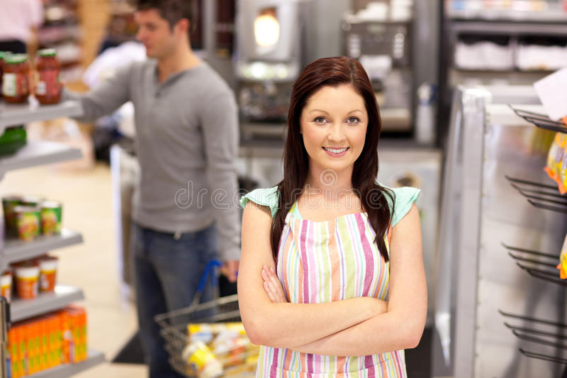 Smiling food retailer with a male customer. Portrait of a smiling food retailer with a male customer in her daily shop at work royalty free stock images