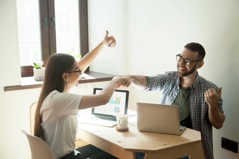 Smiling freelancers giving fists bump and showing thumbs up. Happy with profitable online sales, growing company income, business success on stock market, good stock image