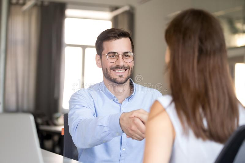 Smiling friendly businessman handshaking woman at job interview, stock images