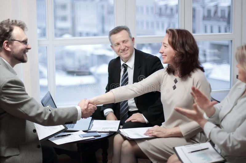 Smiling friendly businessman shaking hands with woman sitting at office desk royalty free stock images