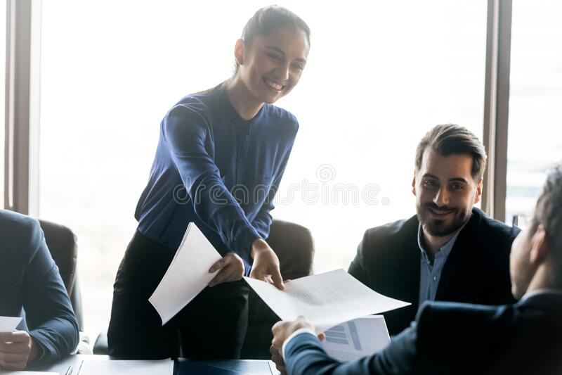 Smiling friendly businesswoman giving handout material to employee at meeting. Smiling friendly businesswoman giving handout material, paper sheet to employee at royalty free stock photos