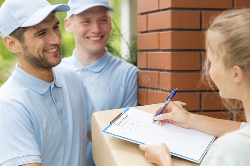 Friendly couriers in blue uniforms and woman signing receipt of package delivery. Smiling friendly couriers in blue uniforms and women signing receipt of package royalty free stock photo