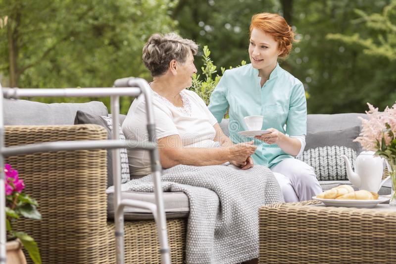Smiling friendly nurse giving tea to elderly woman in the terrace royalty free stock photos