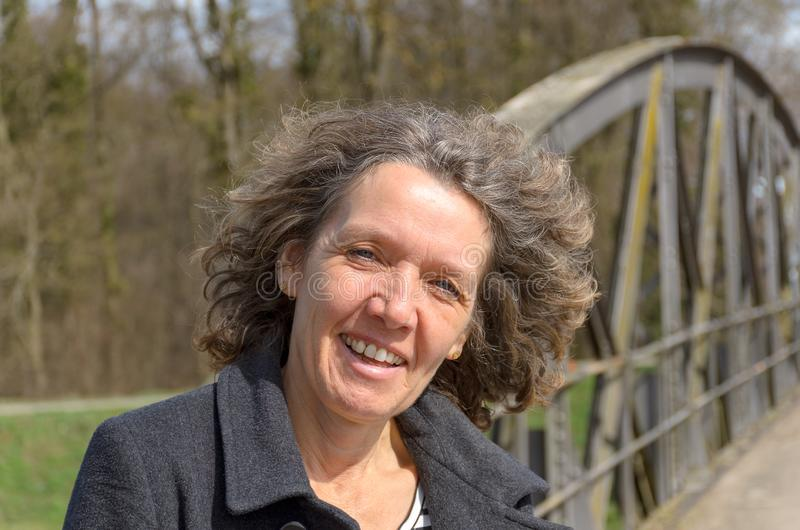 Smiling friendly woman with tousled hair. Standing on a bridge in the countryside in spring sunshine looking at camera with a happy smile stock photo
