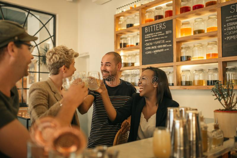 Smiling friends cheering with drinks in a trendy bar. Smiling group of diverse young friends laughing and toasting with drinks while hanging out together in a royalty free stock image