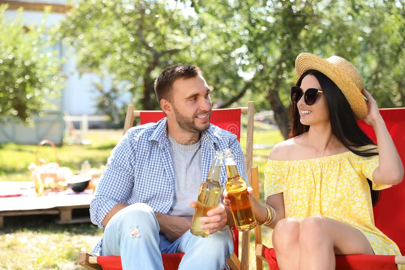 Smiling friends clinking bottles on picnic on summer day stock photos