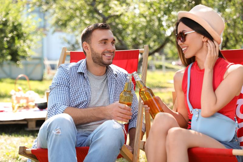 Smiling friends clinking bottles on picnic on summer day stock images