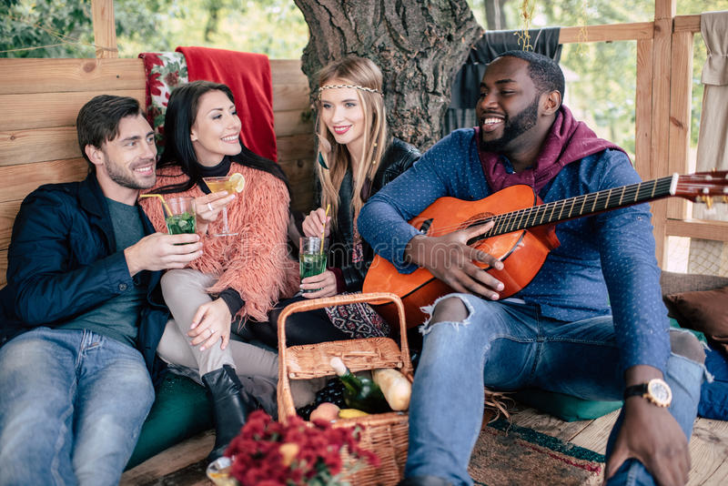 Smiling friends with cocktails enjoying guitar royalty free stock images