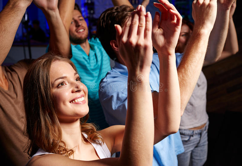 Smiling friends at concert in club. Party, holidays, celebration, nightlife and people concept - smiling friends applauding at concert in club stock photos