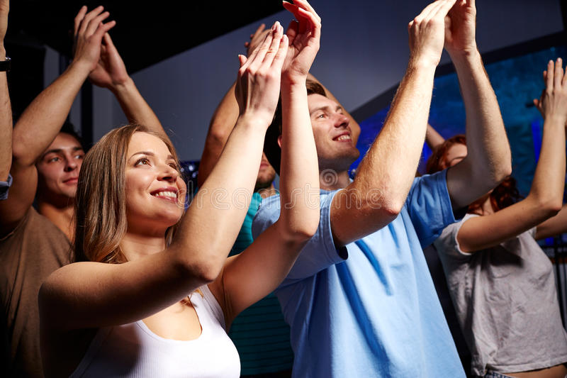 Smiling friends at concert in club. Party, holidays, celebration, nightlife and people concept - smiling friends applauding at concert in club stock photo