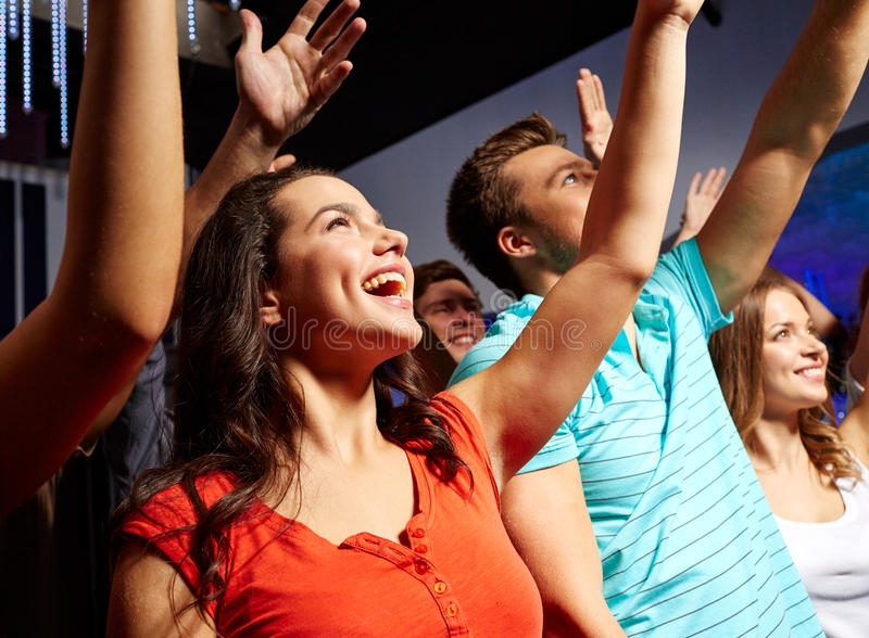 Smiling friends at concert in club. Party, holidays, celebration, nightlife and people concept - smiling friends waving hands at concert in club royalty free stock image